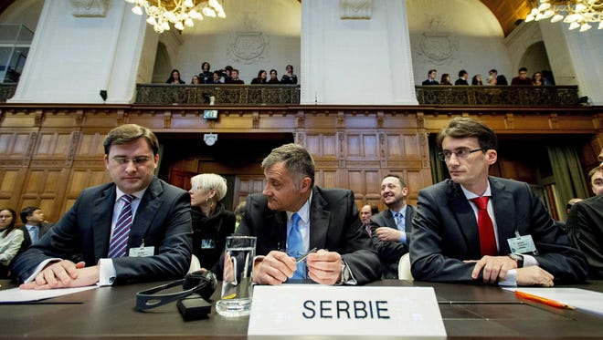 Serbian Justice Minister Nikola Selkovic, left, ambassador Petar Vico and Sasa Obradovic, right, head of the Serbian legal team, listen during the verdict on genocide claims at the U.N. International Court of Justice in The Hague.