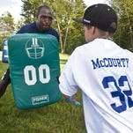 Devin McCourty of the New England Patriots (left) runs a blocking drill with a participant in one of the instructional camps he hosted with his twin brother in 2013.