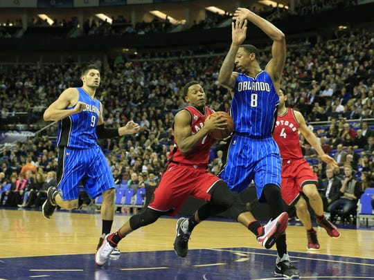 Toronto Raptors guard Kyle Lowry, drives forward as Orlando Magic's Channing Frye (No 8) defends during the second half of an NBA basketball game, at the O2 arena in London, Thursday, Jan. 14, 2016. Raptors won the game 106-103. (AP Photo/Alastair Grant)