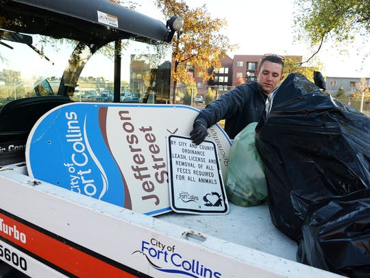 Marshall Loewen puts a sign into a city vehicle at