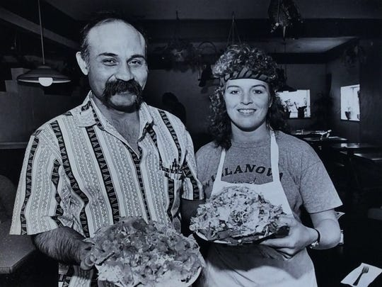 Owner Arturo Santa Cruz, left, holds a plate of nachos while restaurant manager Zsuzsanna Toth holds another El Azteco favorite: Topopo salad, March 12, 1987.