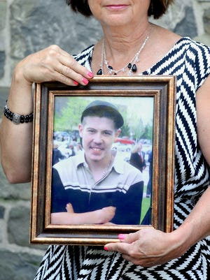 Pat Roza of Milton holds a photograph of her son, Christopher Usifer, who died at age 22 on July 4, 2007, of complications from drug abuse.
