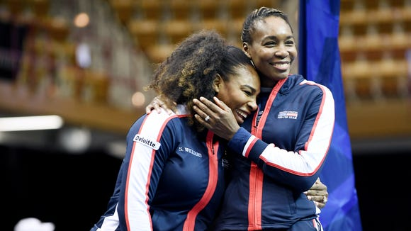 Serena, left, and Venus Williams put their arms around each other during the Fed Cup match draw at the US Cellular Center February 9, 2018.