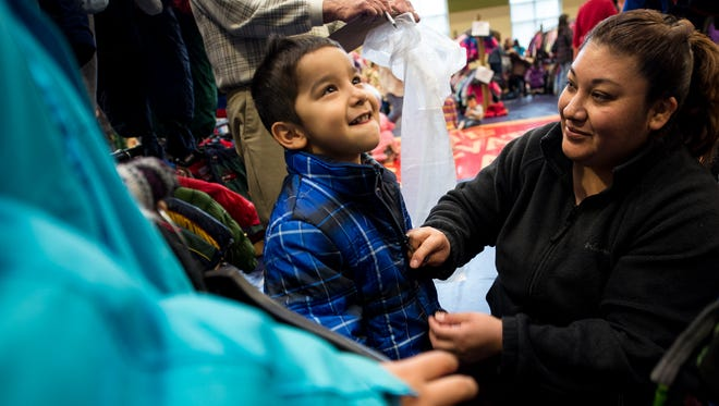 A Coats for Kids recipient tries on a new coat at The Salvation Army's Kroc Center in Green Bay in 2013.