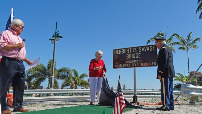 Council chair Bob Brown does the honors as Herb Savage and wife Emily unveil a sign that gives the Smokehouse Bridge a new name - Herbert R. Savage.