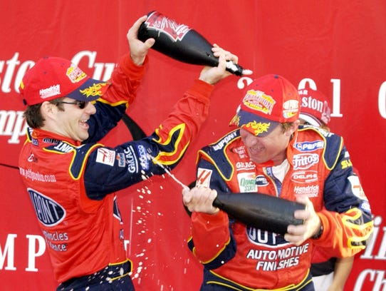 Jeff Gordon, left, and a crew member spray each other