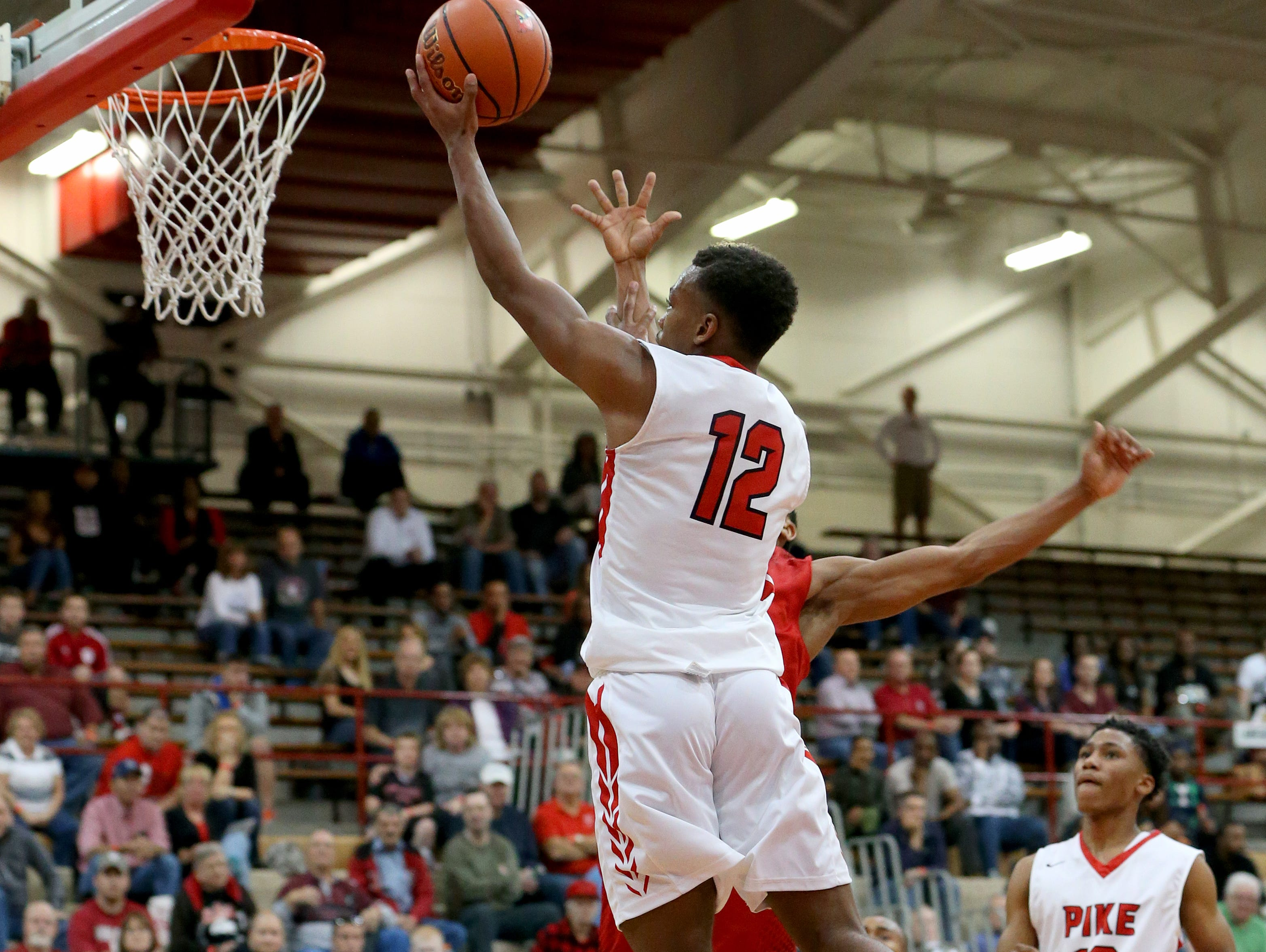 Pike's Justin Thomas (12) hits a layup against New Albany during the Tip Off Classic on Dec. 12, 2015.