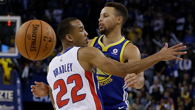 Golden State Warriors' Stephen Curry, right, passes behind Detroit Pistons' Avery Bradley (22) during the second half.