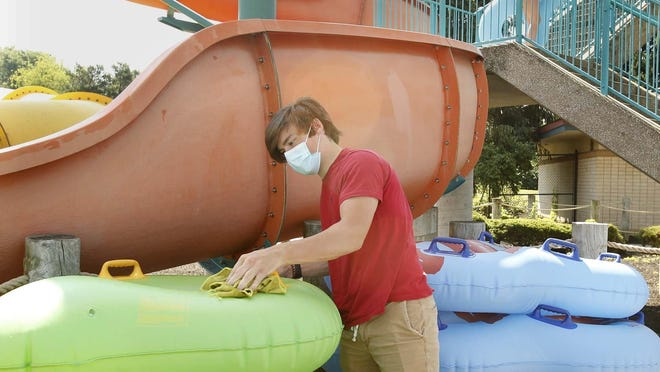 Austin Scharff-Kyle, a guest services employee at Water Works Family Aquatic Center, sanitizes rafts before guests take them down the slides Thursday July 2, 2020 in Cuyahoga Falls, Ohio. The center will be open at half capacity because of the COVID 19 pandemic.