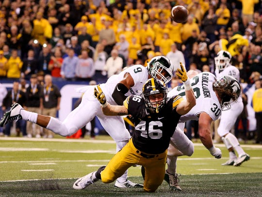 Iowa tight end George Kittle (46) is hit as he attempted a catch in the end zone by Michigan State linebacker Riley Bullough (30) during the Big Ten Championship Game at Lucas Oil Stadium on Dec. 5, 2015. The pass was later intercepted.