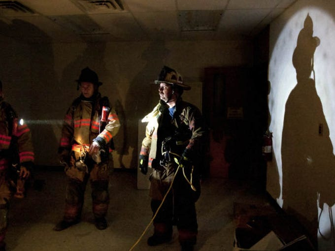 Fort Myers firefighters review a training exercise in the old downtown Fort Myers library.