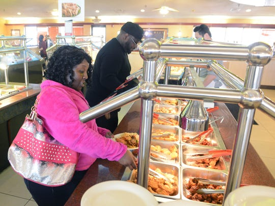 Lula Cooper and Derrie King get food from the buffet