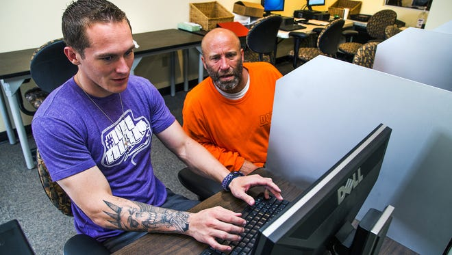 Jesse Dalla Riva, 23, left, helps Phoenix Rescue Mission resident Joshua Day write a resume at the homeless shelter, Wednesday, September 2, 2015. Riva used to be a resident, but after becoming clean and sober and being inspired by what he heard in the on-site chapel, Riva now works part time at the Mission. He also won a full-ride scholarship to Grand Canyon University.