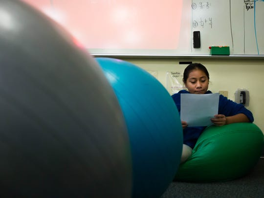 Anayeli Villeda, 10, finds a comfortable spot to read her pen pal letter at Immokalee Community School January 23rd, 2017.