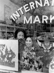 Win and Patti Myint look out the window of the International Market on Belmont Blvd. Feb. 16, 1976.