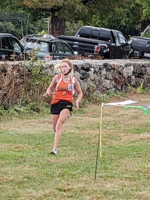 Gardner High's Serenity Rhodes runs toward the finish line during the Wildcats' season-opening cross country meet against the Quabbin Panthers, Friday afternoon, at Mount Wachusett Community College.