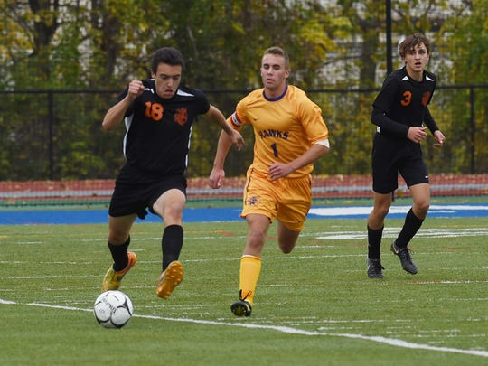 Dover's Brandan Ferrotta, left, takes the ball down the field during Thursday's Class B boys soccer final against Rhinebeck at Middletown High School.
