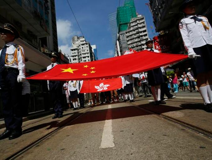 Participants hold a Chinese national flag and a Hong Kong flag as tens of thousands of people march on a down town street to oppose a planned civil disobedience campaign by pro-democracy activists in Hong Kong, Sunday, Aug. 17, 2014. The rally was organized by a pro-Beijing group. Many carried banners or shouted slogans saying they were opposed to the Occupy Central pro-democracy movement.