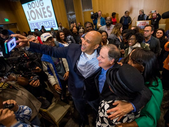 U.S. Sen Cory Booker and Democratic U.S. Senate candidate Doug Jones take selfies with supporters during a rally at Alabama State University in Montgomery, Ala. on Saturday December 9, 2017.