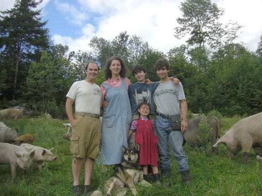 Walter Jeffries, left, stands with his family, dog and pigs on their Sugar Mountain Farm. . .