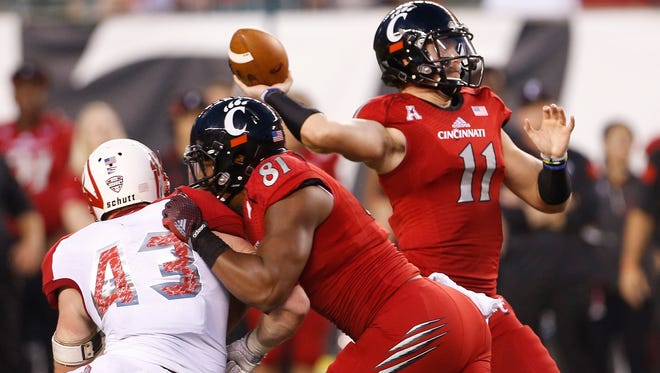 UC's Gunner Kiel gets protection from D.J. Dowdy (81) as he throws a touchdown pass against Miami University on Saturday.
