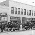 THEN: Gust's Chili Parlor in the 1940's with the  Anheuser-Busch Clydesdale Horse team. The Gust's sign advertises whiskey or wine - 10 cents.  His parlor is flanked by the Ramona movie theatre and S. Hobaica & Son clothing store, owned by a longstanding Lebanese family. The site at 311 East Washington was first opened by Gust Metsopolos in 1923 as a fruit and sandwich shop.