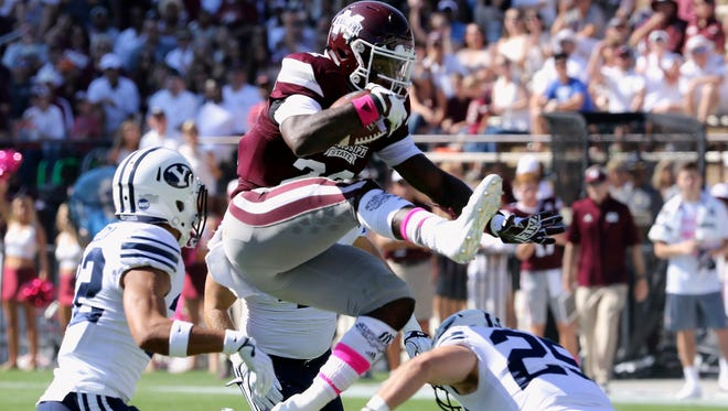 Mississippi State running back Aeris Williams (22) hurdles over BYU defensive back Tanner Jacobson (25).