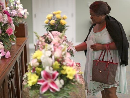 Althia Burt lays her hand on the casket of Baby Jane