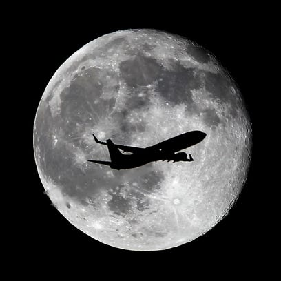 A United Airlines passenger plane crosses the waning