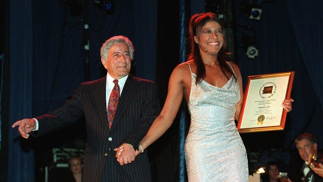 "Singer/songwriter Natalie Cole, right, walks off stage after receiving ""The Hitmaker's Award"" from legendary vocalist Tony Bennett, at the Songwriter's Hall of Fame Wednesday, June 9, 1999, in New York. Cole is the daughter of the late vocalist Nat King Cole. (AP Photo/Stuart Ramson)"