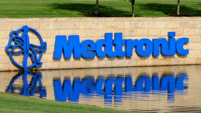 Medical device maker Medtronic's logo reflects in the pond in front of the corporate headquarters Tuesday, Aug. 24, 2010 in Fridley, Minn. Medtronic Inc. said Tuesday its fiscal first-quarter earnings jumped to $830 million but revenue fell. (AP Photo/Jim Mone)