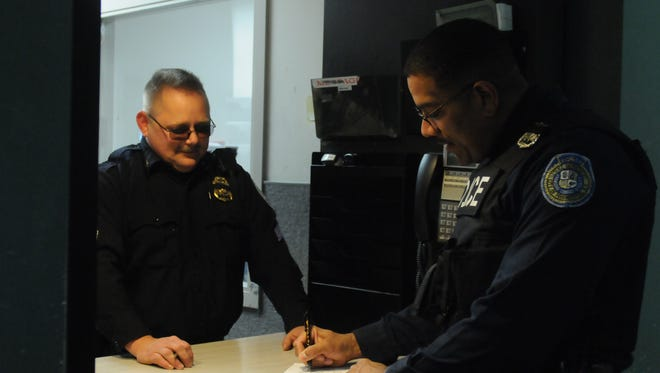 Sgt. Bryan Cronk, left, and Officer Paul Featherston, right, stand at the booking desk of the City of Poughkeepsie Police Department.