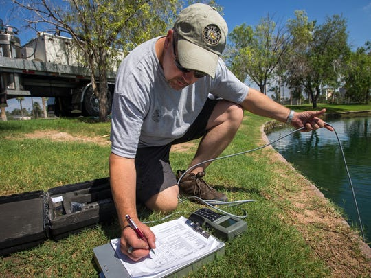 Scott Gurtin, manager of the Arizona Game and Fish Department's community fishing program, writes down the values of the water before restocking nearly 500 lbs of channel catfish in the lake at Encanto Park on Friday, September 19, 2014. Roger Coffman, owner of Mr. Fish, delivers the tons of catfish to restock the city's lakes, from his facility in Arkansas. The City of Phoenix, with the assistance of the Arizona Fish and Game Department, will spend about $50,500 to stock fish at seven sites for the community-fishing program this fiscal year.