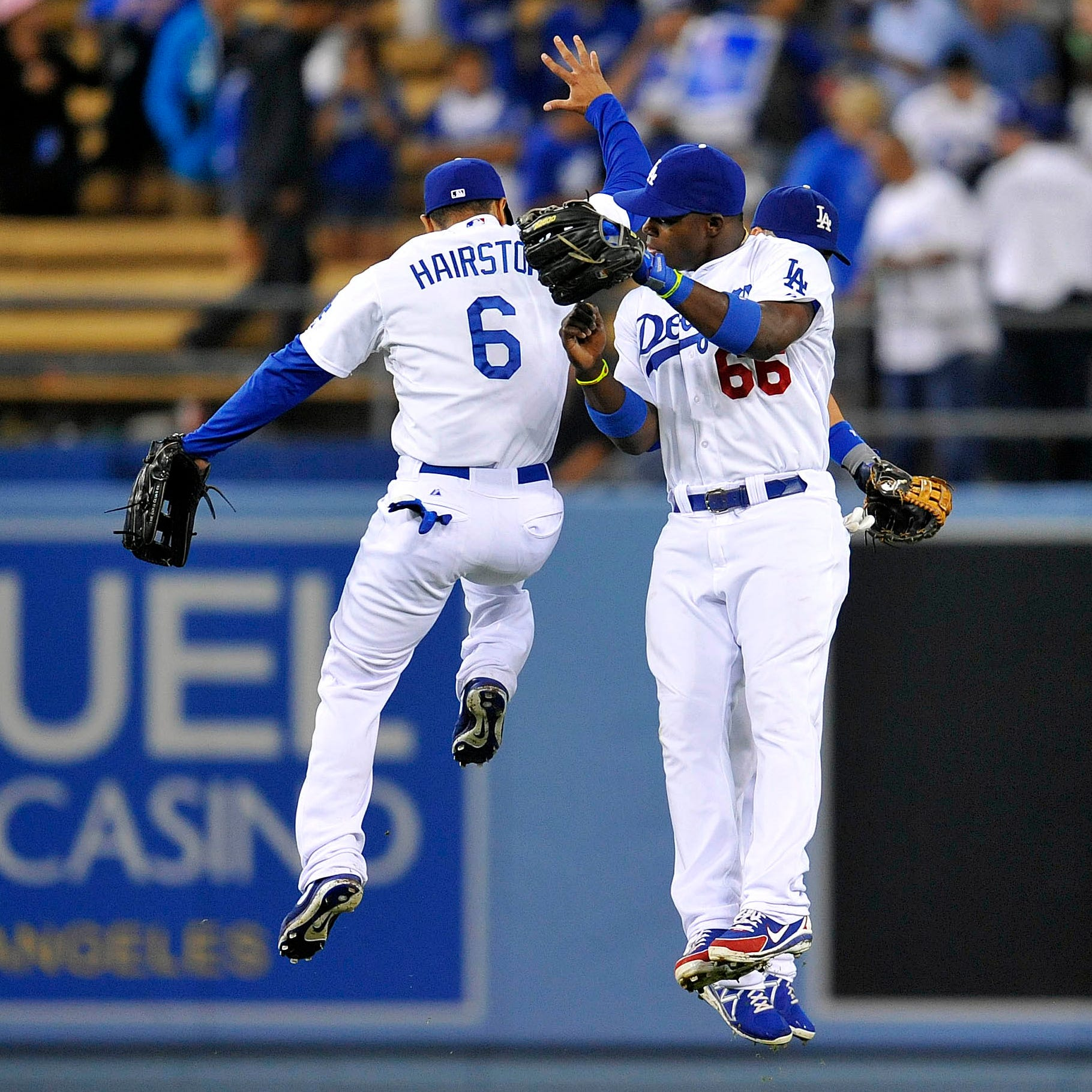 Los Angeles Dodgers center fielder Jerry Hairston Jr., left, right fielder Yasiel Puig, right, and left fielder Skip Schumaker celebrate the victory against the Mets.