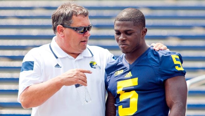 Michigan head coach Brady Hoke, left, speaks with freshman cornerback Jabrill Peppers (5) after a team photo during the NCAA college football team's preseason media day, Sunday, Aug. 10, 2014, at Michigan Stadium in Ann Arbor, Mich.