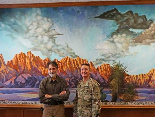Artist Robert Glaisek poses in front of his mural with
