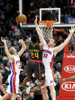 Hawks guard Kent Bazemore attempts a shot against Pistons guard Steve Blake (22) and forward Aron Baynes (12) in the second quarter of their game at Philips Arena on Tuesday.