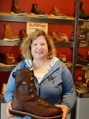 Store co-owner/manager Kelly Church holds a size 14 boot at the Red Wing Shoe store, Wednesday, August 9, in Sheboygan. Church says that the store has become a destination for many shoe purchasers.