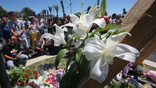 Floral tributes are laid out near the site of the truck attack in the French resort city of Nice, southern France, Friday, July 15, 2016. France has been stunned again after a large white truck killed many people after it mowed through a crowd of revellers gathered for a Bastille Day fireworks display in the Riviera city of Nice. (AP Photo/Luca Bruno)