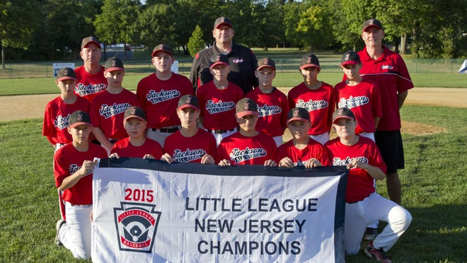 The Jackson Little League team poses with its state championship banner Friday.