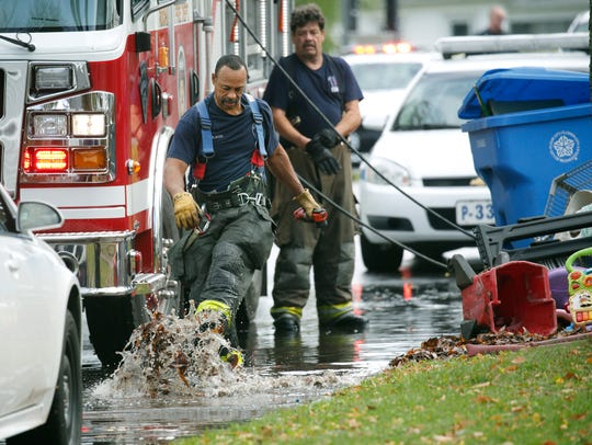 Rochester firefighters clean up the scene of a fatal