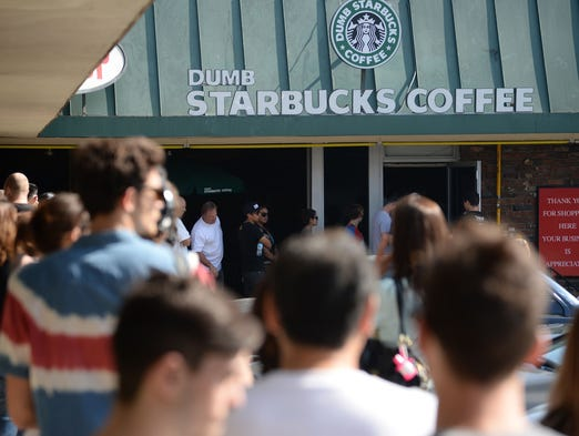 "People wait in a long line to get into a coffee shop named ""Dumb Starbucks"" in the Los Feliz area of Los Angeles. The store resembles a Starbucks with a green awning and the Starbucks logo, but with the word ""Dumb"" added before ""Starbucks.""  All food and drink in the store is free."