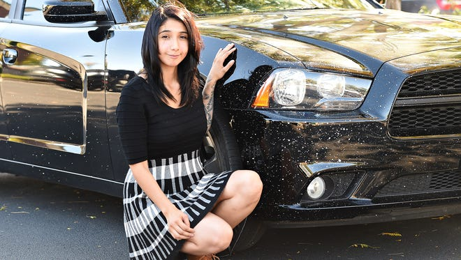 Kristen Llamas' new car was splattered with paint when she drove by workers painting stripes on Timberline Road in Fort Collins. Now she's suing the city over the damage.