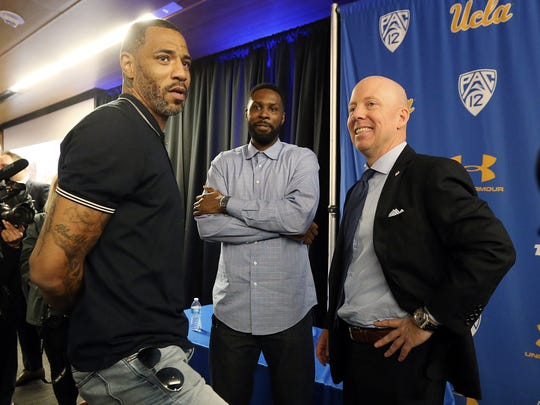 Mick Cronin, right, chats with Cincinnati and NBA star Kenyon Martin, left, and Ronald Allen, who played for Cronin at Cincinnati from 2005 to 2007, after Cronin was introduced as the UCLA's new head basketball coach at a news conference on the campus in Los Angeles Wednesday, April 10, 2019. Cronin was hired as UCLA's basketball coach Tuesday, ending a bumpy, months-long search to find a replacement for the fired Steve Alford. The university said Cronin agreed to a $24 million, six-year deal. (AP Photo/Reed Saxon)