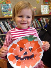 """Aria Norenberg, age 2, of Oakfield shows off the pumpkin she made as part of Oakfield Library storytime on Oct. 7. The theme was """" A Round and Around."""" Children also enjoyed slightly spooky Halloween stories and snacks."""