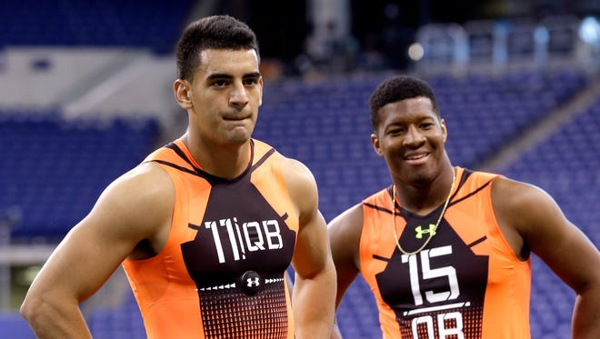 Oregon quarterback Marcus Mariota (11) and Florida State quarterback Jameis Winston (15) wait to run a drill Saturday at the NFL football scouting combine in Indianapolis.