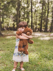 Olivia holds a bear with her baby brother's heartbeat inside.