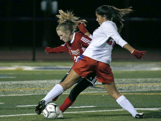 Fairport's Emily Racaniello and Penfield's Jordan Egger battle for the ball in the first half at Pittsford Sutherland High School.