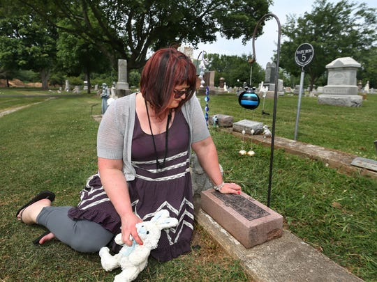 Indy Jo Wood, 40, Chicago, sits by her brother Billy's grave in Greenlawn Cemetery, Franklin.