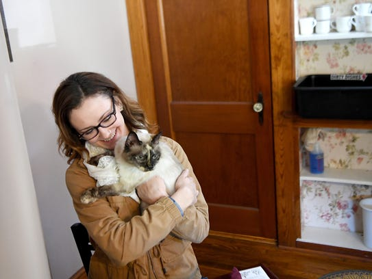 Rose Saunders hugs Matilda the cat at her table during